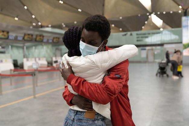 Echtparen dragen gezichtsmaskers die elkaar omhelzen