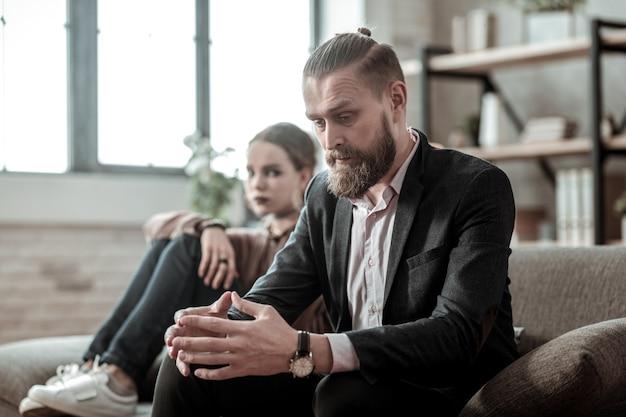 Echtscheiding met vrouw. bebaarde vader voelt zich emotioneel terwijl hij met zijn vrouw over echtscheiding spreekt tegen zijn dochter