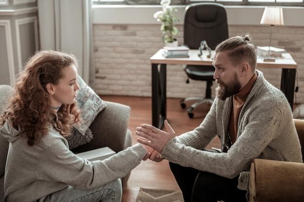 Echtscheiding van ouders. bebaarde vader praat met zijn dochter en legt de scheiding uit met haar moeder