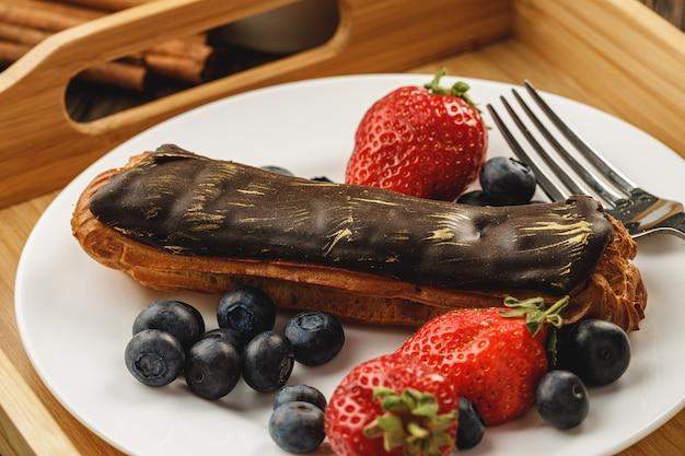 Eclair cake met chocolade glazuur op houten dienblad
