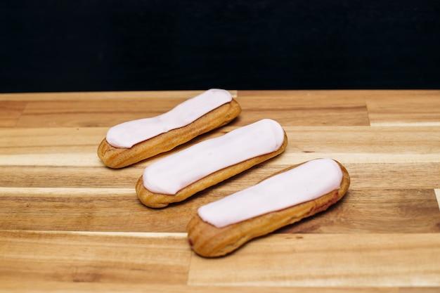 Eclair knapperige romige cake met witte chocolade geïsoleerd op houten oppervlak