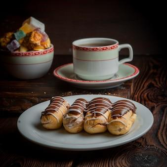 Eclair met suiker en kopje thee in plaat