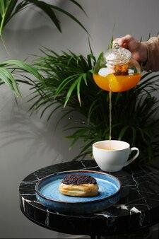 Eclair op keramische plaat en kopje thee op marmeren steen en tropische planten op achtergrond. theepot gieten. vrouw hand houden theepot. thee plons.