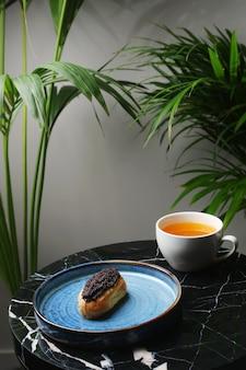 Eclair op keramische plaat en kopje thee op marmeren steen en tropische planten op achtergrond.