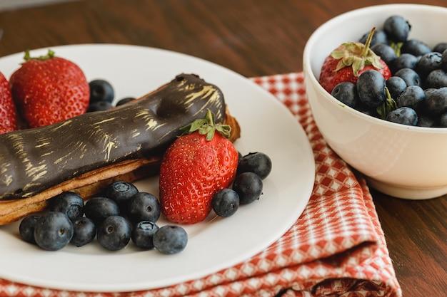 Eclaircake met chocoladeglans op houten dienblad