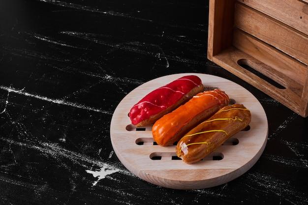Eclairs met fruitsauzen bovenop geserveerd op een houten bord.