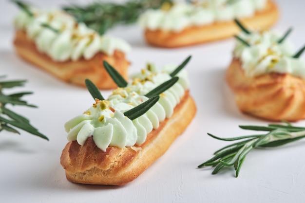 Eclairs met pistachecrème en frambozenvulling, gegarneerd met gemalen pistache en rozemarijn.