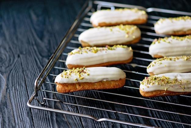 Eclairs met witte chocoladeglazuur en pistachenoten op een gebakrek op donkere achtergrond