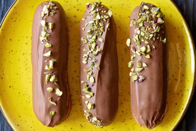 Eclairs of soesjes met melkchocolade glazuur en pistachenoten op een gele plaat close-up