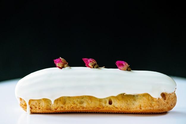 Eclairs of soesjes met witte chocoladeglazuur met rozensmaak op witte en zwarte achtergrond