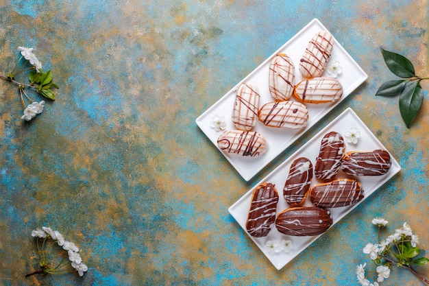 Eclairs of soesjes met zwarte chocolade en witte chocolade met vla binnen, traditioneel frans dessert. bovenaanzicht.