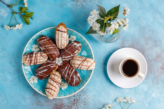 Eclairs of soesjes met zwarte chocolade en witte chocolade met vla erin, traditioneel frans dessert. bovenaanzicht.