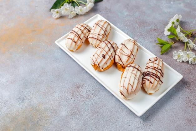 Eclairs of soesjes met zwarte chocolade en witte chocolade met vla erin, traditioneel frans dessert.