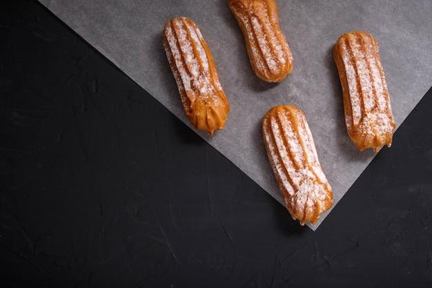 Eclairs, taarten op een donkere achtergrond. patroon