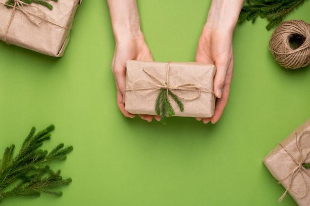 Eco aanwezig met groene planten in kraftpapier in handen op een groen oppervlak