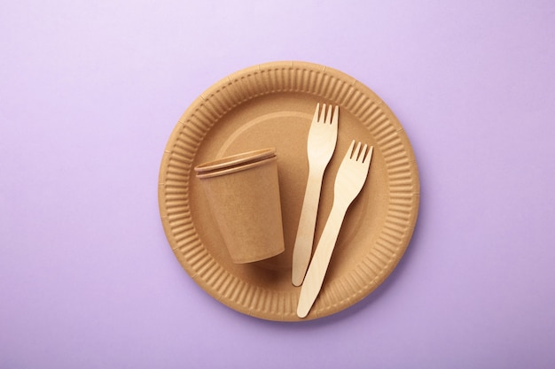 Eco ambachtelijk papier servies. papieren bekers, borden, tas, fastfoodcontainers en houten bestek op paarse achtergrond. zero waste. recyclingconcept. ruimte kopiëren