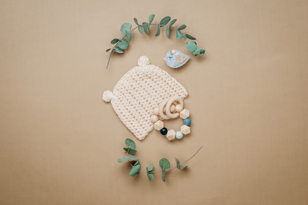 Eco babyaccessoires concept. houten bijtring en babymutsje op beige achtergrond met lege ruimte voor tekst. bovenaanzicht, plat gelegd.