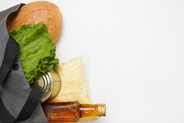 Eco boodschappentas met voedingsmiddelen op witte achtergrond met kopie ruimte