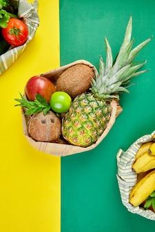 Eco boodschappentassen met biologische groenten en fruit op gele achtergrond.