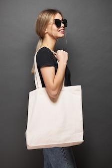 Eco-draagtas voor mockup wordt vastgehouden door een vrouw over grijze textuur