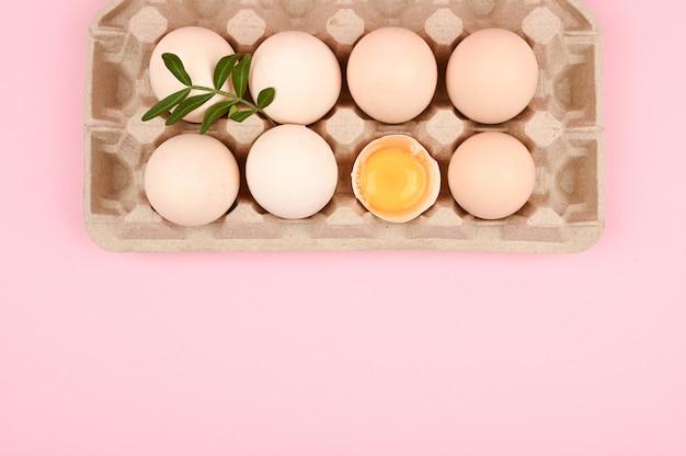 Eco-eieren op een roze achtergrond. een lade van eieren op een witte en roze achtergrond. eco dienblad met testikels. minimalistische trend, bovenaanzicht. eiertray. pasen concept.