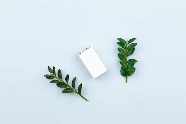 Eco-energie of groene stroom illustratie met een witte batterij en takjes bladeren op een lichte achtergrond met kopie ruimte voor tekst.
