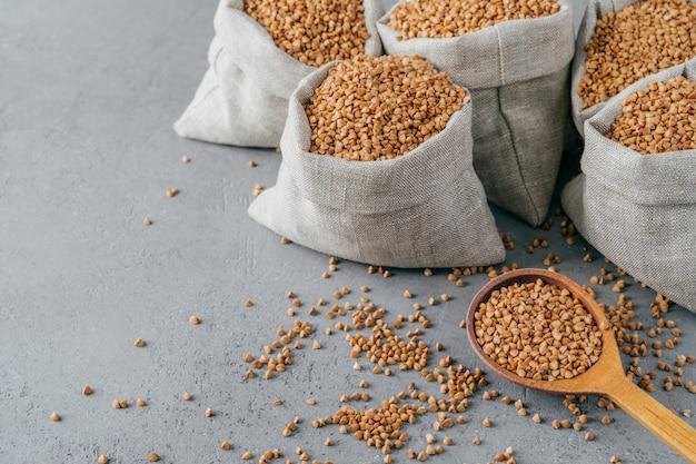 Eco-eten en schoon eten concept. boekweit in kleine linnen zakjes. houten lepel gevuld met eiwitproduct, kopie ruimte op grijze achtergrond.