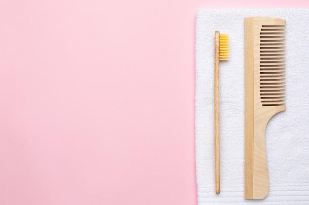Eco houten tandenborstel, kam en witte badhanddoek op roze