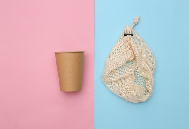 Eco katoenen tas en kartonnen beker op roze blauwe achtergrond. milieuvriendelijk concept. bovenaanzicht
