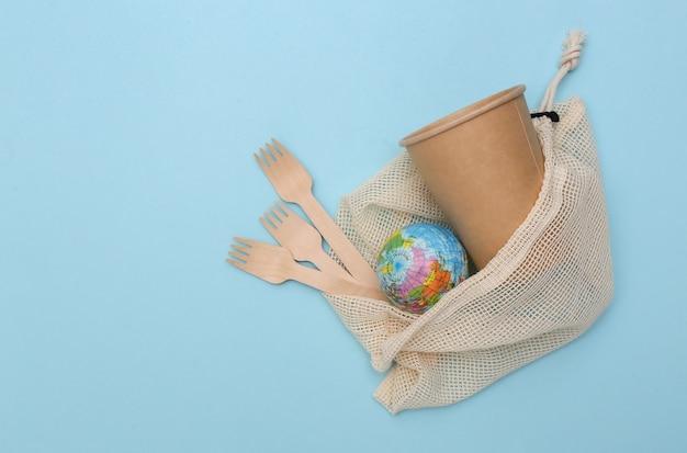 Eco katoenen tas met houten lepels en kartonnen beker, globe op blauwe achtergrond. milieuvriendelijk concept. red planeet.