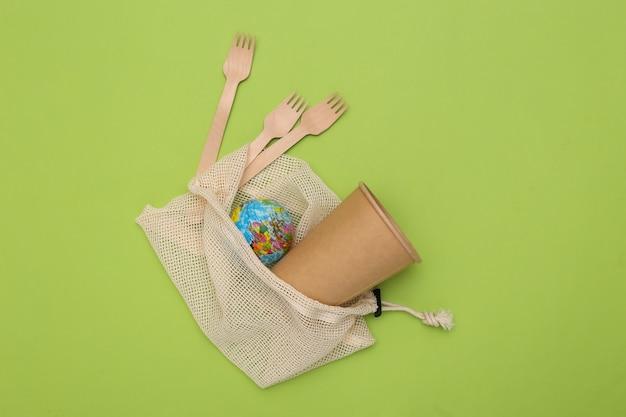 Eco katoenen tas met houten lepels en kartonnen beker, globe op groene achtergrond. milieuvriendelijk concept. red planeet.