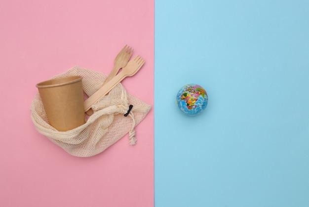 Eco katoenen tas met houten lepels en kartonnen beker, globe op roze blauwe achtergrond. milieuvriendelijk concept. red planeet. bovenaanzicht
