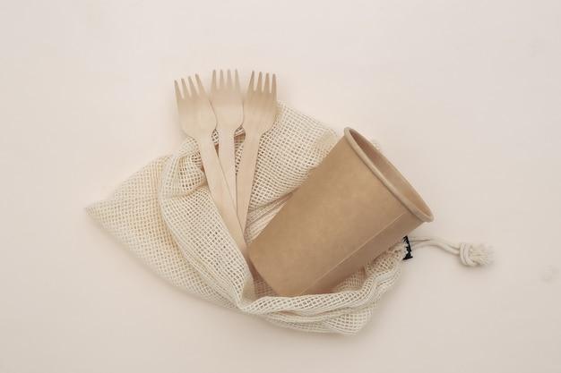 Eco katoenen tas met houten lepels en kartonnen beker op beige achtergrond. milieuvriendelijk concept. bovenaanzicht