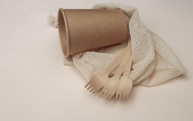 Eco katoenen tas met houten lepels en kartonnen beker op beige achtergrond. milieuvriendelijk concept.