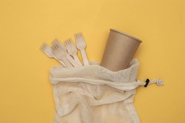Eco katoenen tas met houten lepels en kartonnen beker op gele achtergrond. milieuvriendelijk concept. bovenaanzicht