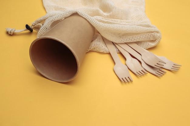 Eco katoenen tas met houten lepels en kartonnen beker op gele achtergrond. milieuvriendelijk concept