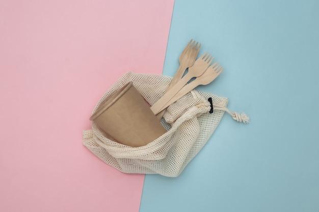 Eco katoenen tas met houten lepels en kartonnen beker op roze blauwe achtergrond. milieuvriendelijk concept. bovenaanzicht