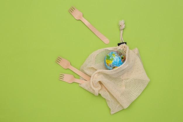 Eco katoenen tas met houten lepels, globe op groene achtergrond. milieuvriendelijk concept. red planeet.