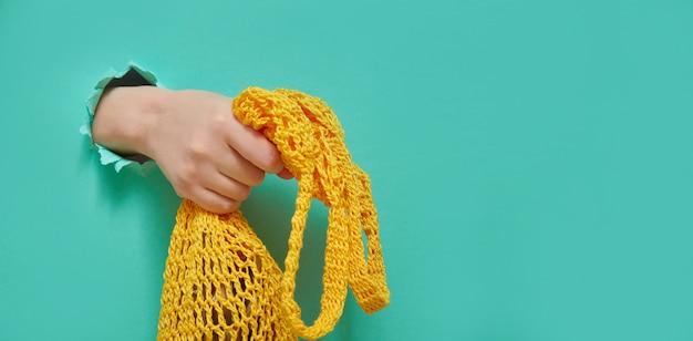 Eco mesh string bag in handen van de vrouw uit een rond gat in groenboek achtergrond. trendbanner voor elke winkel of markt. creatief concept met kopie ruimte. Premium Foto