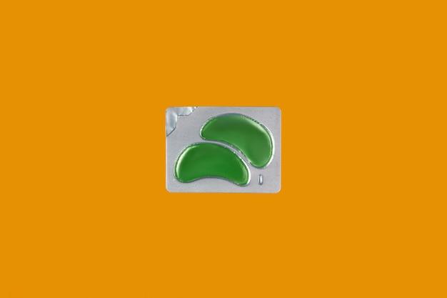 Eco ooglapjes op oranje achtergrond gezichtsverzorging schoonheidsbehandeling concept