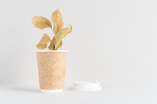 Eco-papieren koffiekopje met prachtige plant in een concept zonder afval