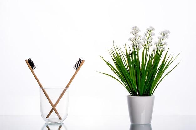 Eco-tandenborstels gemaakt van hout in een glazen glas op een tafel met een groene tak