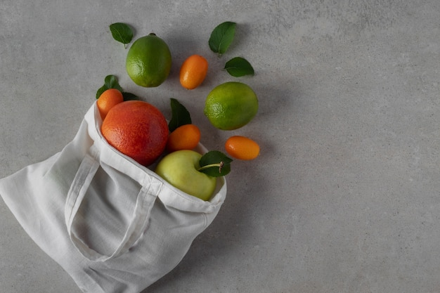 Eco tas en verspreide tropische vruchten op grijze tafel, plat leggen. kopieer ruimte