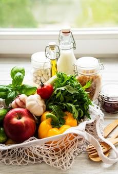 Eco-tas met fruit en groenten, glazen potten met bonen, pasta, melk en olie