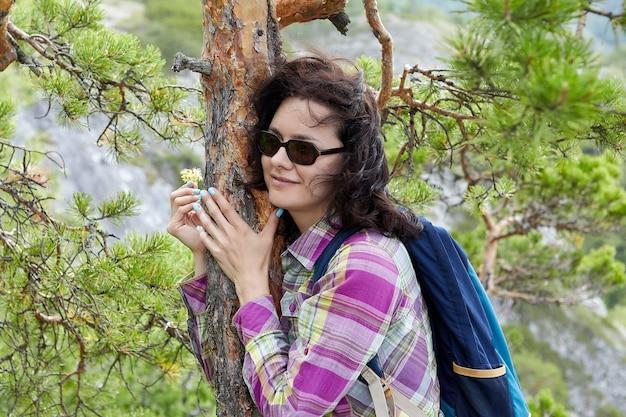 Eco-toerisme in de bergen, mooie vrouw in zonnebril en met rugzak op haar rug, dennenboomstam knuffelen.