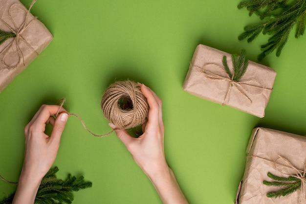 Eco touw in handen en geschenken met groene planten in ambachtelijke papier op groen oppervlak