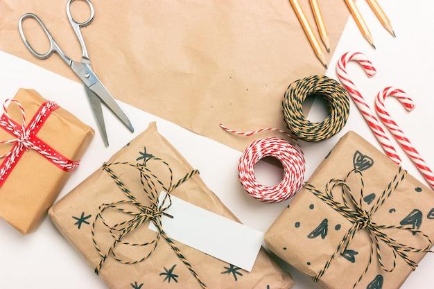 Eco-verpakking van cadeaus voor kerstmis en nieuwjaar. dozen, gestreepte koord, linten, schaar, etiketten, envelop, snoeplolly. plaats voor tekst