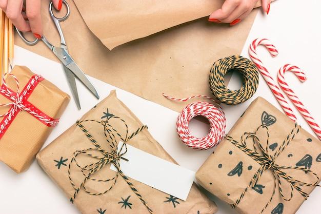 Eco-verpakking van cadeaus voor kerstmis en nieuwjaar. vrouwelijke handen houden schaar en papier