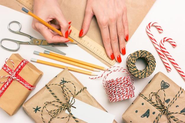 Eco-verpakking van cadeaus voor kerstmis en nieuwjaar. vrouwelijke handen meten de maat met een potlood en liniaal