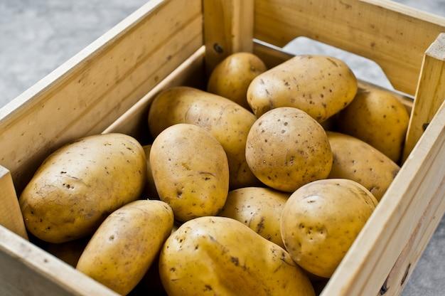 Eco-verpakking voor groenten, plastic vrij. aardappelen in een houten kist, supermarkt.